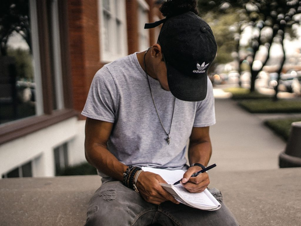 Guy writing in a notebook