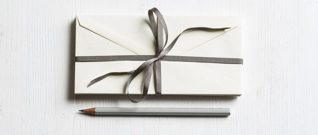 envelopes wrapped in a ribbon with a pencil